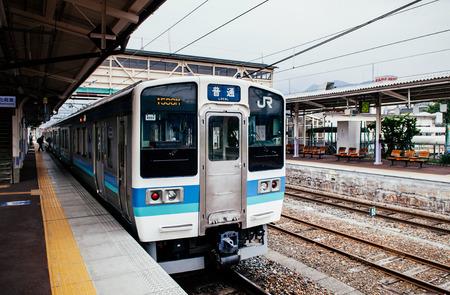 MAY 28, 2013 Shinano Omachi, Nagano, Japan - Local JR train line stop at platform of Shinano Omachi station with Japanese passengers on platform