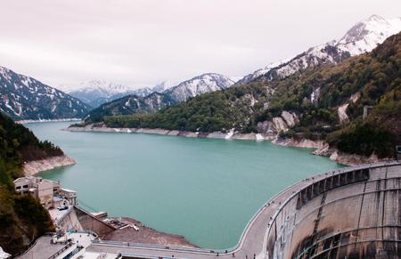 Nature scene on Kurobe dam between mountains with green turqouise lake, part of Tateyama Kurobe Alpine route Stock Photo