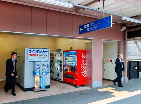 MAY 27, 2013 Toyama , Japan - Japanese man in office uniform using coin locker with beverage vender maching at JR Toyama train station people walking pass by