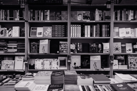 DEC 18, 2013 Singapore - Many kinds of book display on wooden bookshelves in local bookshop. Black and white image