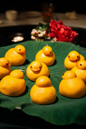 Yellow cute duck shaped Baozi chinese steamed bun on lotus leaf in restaurant 版權商用圖片