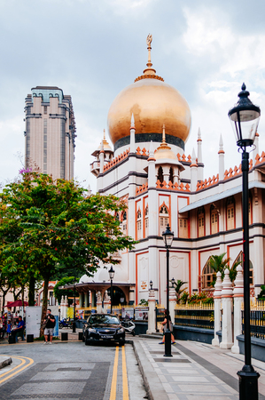 DEC 18, 2013 Singapore - Golden dome of Masjid Sultan or Sultan mosque in Kampong Glam, shopping street in Rochor district with colonial buildings and palm tree.