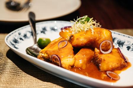 Close up shot of Fried red snapper fish with citrus Kumquat orange sauce - Singaporean cuisine