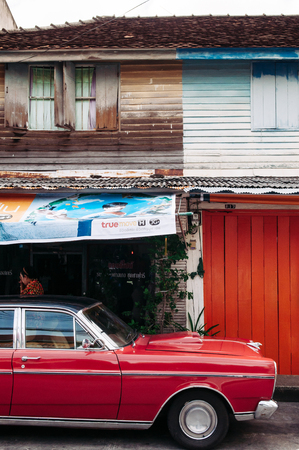 FEB 28, 2013 Songkhla, TAHILAND - Vibrant vintage sport car and old local style wooden house in Songkhla old town. Nang Ngam street famous historic district. Editorial