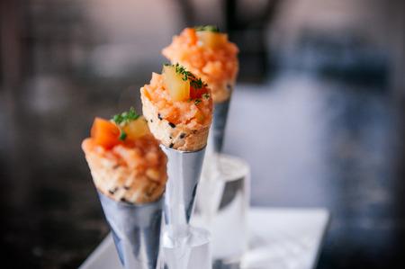 Fresh raw jouicy Salmon Tartare with tomato in mini waffle cones modern creative cuisine, close up shot