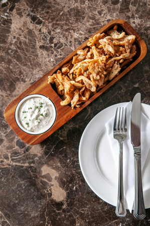 Crunchy deep fried calamari with Tartar sauce in hard wood plate on marble table, close up topview shot