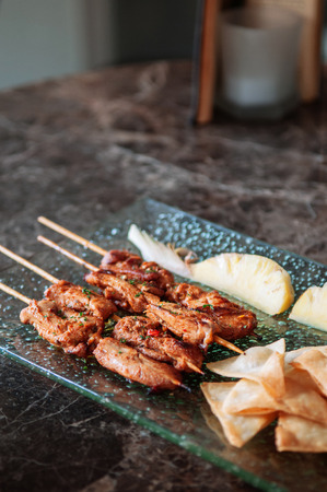 Thai spicy tender pork barbeque skewers with grill pineapple and Papadum crispy chips in glass plate on black marble table