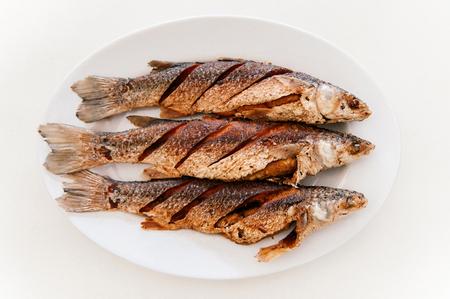 Thai style deep fried Mullet fishes on white plate and white table, Top view shot