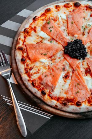 Delicious smoked Salmon thin crispy italian pizza with premium black Caviar close up top view shot