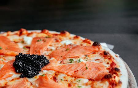 Delicious smoked Salmon thin crispy italian pizza with premium black Caviar close up shot