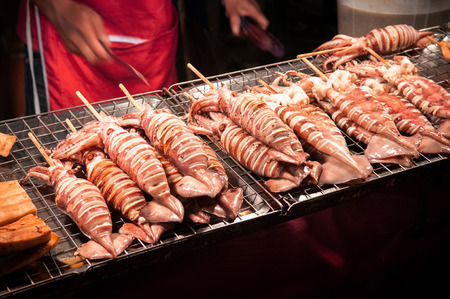 Big Grill squids skewer at street food stall in local night market of Bangkok, Thailand