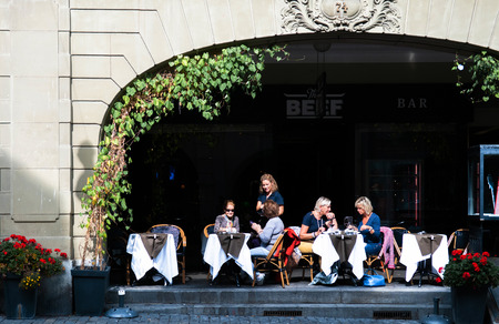 SEP 27, 2013 Bern, Switzerland - European tourists having lunch in street restaurant with outdoor table under beautiful sunlight in old town Bern.