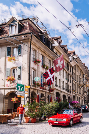 SEP 27, 2103 Bern, Switzerland - Red luxury car on Nydaggasse street, Swiss residential building with Swiss flag and street sign in Old town district of Bern