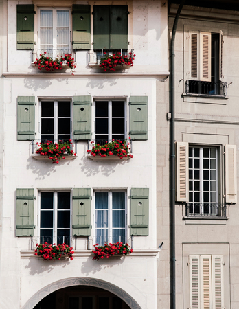 Beautiful white concrete building window with red flower in old town area of Bern