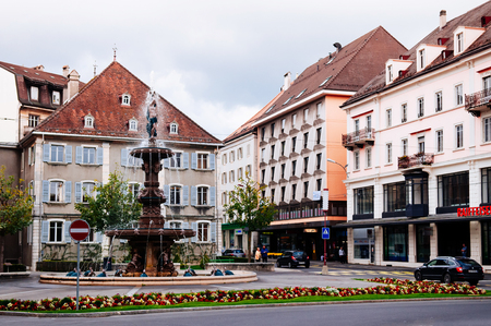 26 SEPTEMBRE 2013 Neuchâtel, Suisse - Ancien bâtiment vintage coloré de la ville de La Chaux de Fonds et fontaine monumentale, le centre le plus important de l'industrie horlogère suisse