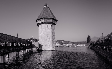 Lucerne medieval Chapel Bridge in bright clear sky evening and old vintage building in background, Switzerland Stock Photo
