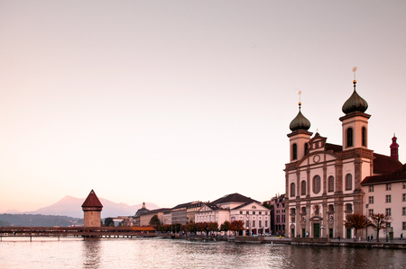 Lucerne Chapel Bridge and Jesuitenkirche at sunset and sweet evening sky with Mount Riki in background, Switzerland