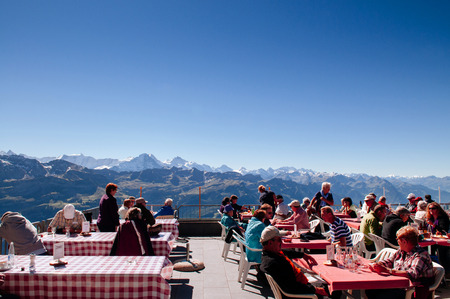 SEP 23, 2013 Entlebuch, Switzerland - Tourists at outdoor luch area on scenic terreace of Mount Brienzer Rothorn with Swiss Alps view under bright sunlight 에디토리얼