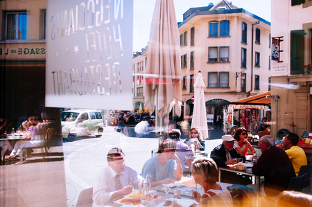 SEP 25, 2013 Vevey, Switzerland - Tourists enjoy outdoor luch with Beautiful vintage buildings in old town area of famous Vevey city Editöryel