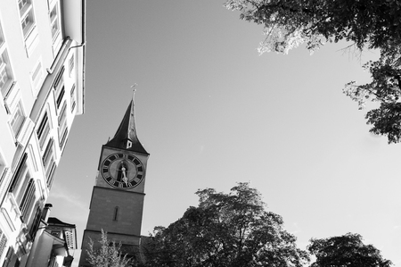 - Beautiful old medieval clock tower against sky in Zurich Old town Altstadt