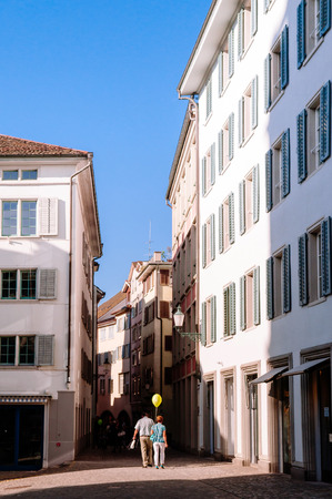 Beautiful old vintage buildings and tourists walking in small alley in Zurich Old town Altstadt area