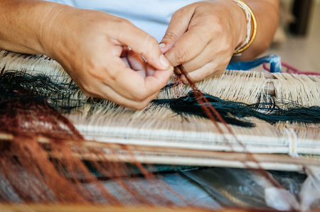 Traditional Thai north eastern style loom details woman hands weaving Thai silk with wooden reeds close up shot Banque d'images