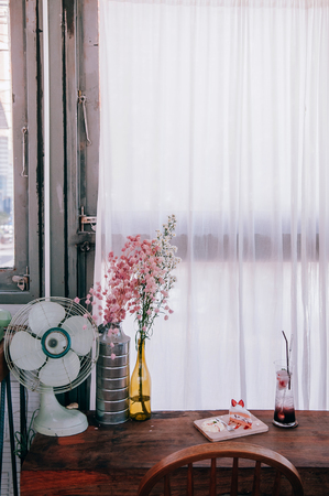 Dried flower white indy home cafe decoration vintage hips style with retro fan, curtain. Old wood table with cake bakery and drink. Stock Photo