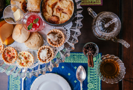 Traditional elegance English afternoon tea with scone, assorted tart and puff pastries on old wood table with tea pot and tea cup top view