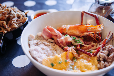 Thai seafood noodle with pork, bacon, river prawn, crispy fried mushroom and condiments set on polka dot tablecloth