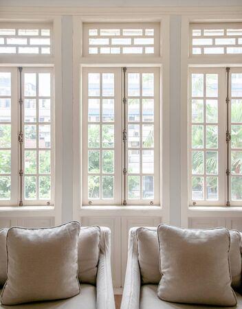 Weißes koloniales Vintage-Wohnzimmer mit Sesseln und klassischem minimalistischem Design-Kissen, gemütliches Zimmer mit Tageslicht durch die Fenster