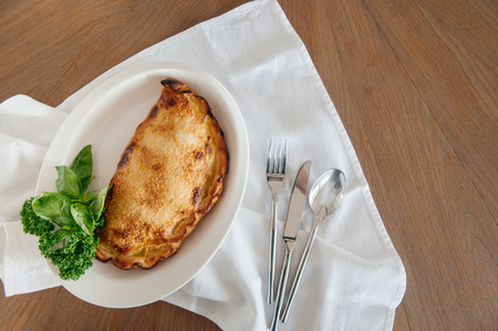 Ham cheese mushroom Calzone pizza with basil leaves, parsley and silverware on wood table. Top view shot with copy space Stock Photo