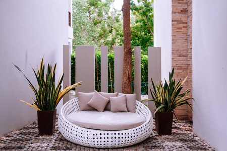 Modern furniture, outdoor rattan sofa couch and plant pots with garden scene on background