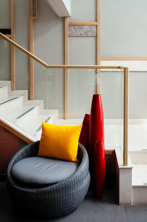 Colourful modern furniture, rattan chairs and vase at stairwell hall in modern building with natural light