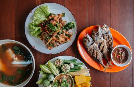 Nam Prik Pla To, fried fish, Spicy fish salad, Tom Yum soup - Thai street food lunch set and fresh vegetables, pumpkin, cucumber, bean and cauliflower