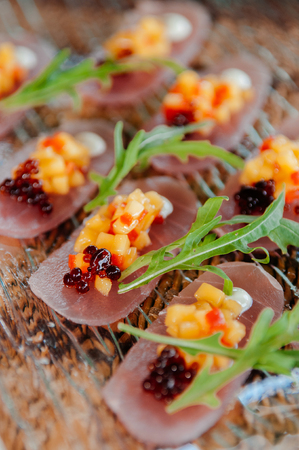Light healthy appetizer - Fresh snapper Tataki with mango salsa and arugulas on glass plate on bamboo mat. Close up shot