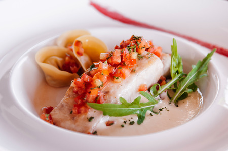 Beautiful fresh Grilled sea bass fillet with tortellini pasta and salsa in white plate. Close up shot