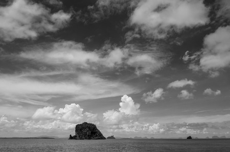 Small rock island near Koh Lanta, Krabi on clear blue sky day, calm Andaman sea in Thailand - Black and white