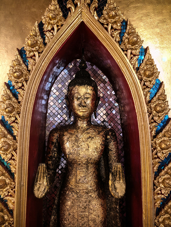 Golden antique old standing buddha statue in Thai Temple with beautiful ornamental frame and golden wall
