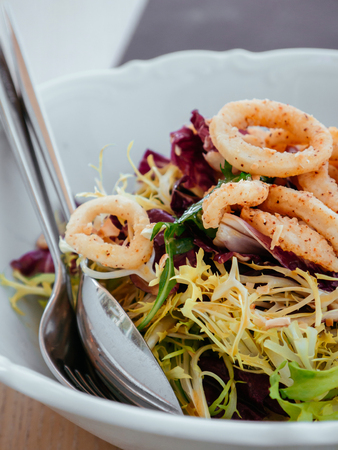 Crispy Fried Calamari and fresh Frisee Radicio mix green salad in white bowl with fork and spoon