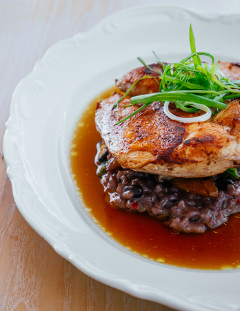Grilled spicy herbal Chicken breast with brown Risotto truffle in clear broth top with spring onion