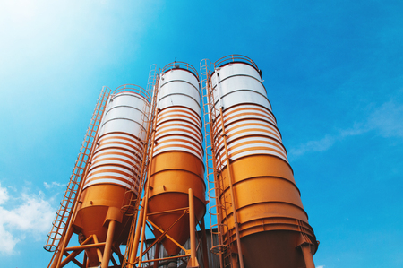 Cement silos of Cement batching plant factory against afternoon sun with clear blue sky Stock Photo