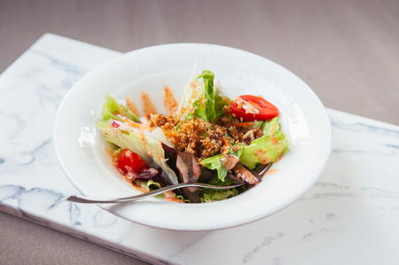 Fresh green mix salad with crispy crumb in white bowl on marble tray and gray fabric background