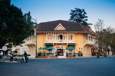 FEB 26, 2014 Dalat, Vietnam - Warm atmosphere and light traffic street evening in Da Lat city with yellow colonial building