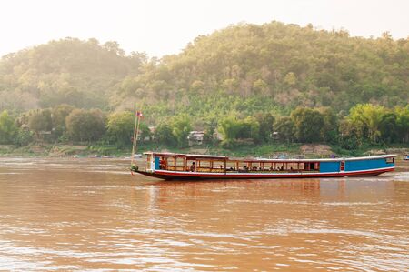 Vintage colourful wooden boats in yellow Mekong river during summer with soft evening light