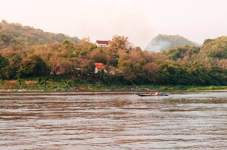 Small Row boat with monks in Mekong river with mountain top temple during summer with soft evening light Banco de Imagens