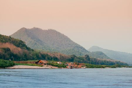 Evening rural village scene and peaceful Mae Khong river with mountain forest in Luang Prabang - Laos Banco de Imagens