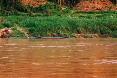 Luang Prabang, Laos - Asian local fisherman boat in yellow water and rural scene of Mae khong river with green shoreline Banco de Imagens