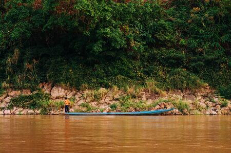 \Asian local fisherman on blue wooden boat and rural scene of Mae khong river with lush green shoreline