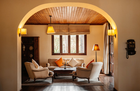 FEB 25, 2014 Dalat, Vietnam - Vintage colonial tropical living room hard wood floor and ceiling with sofa couch, classic lamps and curtain. Furnished with wooden coffee table, colourful pillows and retro telephone Editorial