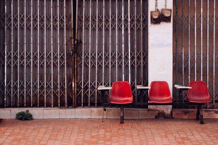 Alte Retro-rote Vorlesungsreihensitze und altes rustikales Gebäude mit Metalltor und leerem Bürgersteig